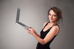 Jovem mulher que guarda o laptot moderno Foto de Stock