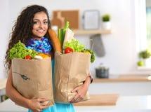 Jovem mulher que guarda o saco de compras na mercearia com Imagens de Stock Royalty Free