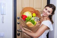 Jovem mulher que guarda o saco de compras na mercearia com vegetais O packege de papel está completo do alimento Imagens de Stock Royalty Free