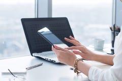 Jovem mulher que guarda o tablet pc moderno, usando o dispositivo no local de trabalho durante a ruptura, a conversa, blogging e  fotos de stock