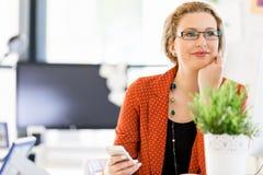 Jovem mulher que guarda o telefone celular no escritório Fotos de Stock Royalty Free