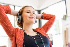 Jovem mulher que guarda o telefone celular no escritório Imagens de Stock Royalty Free