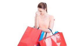 Jovem mulher que guarda os sacos de compras que têm a dor de cabeça ou que são stres Imagens de Stock