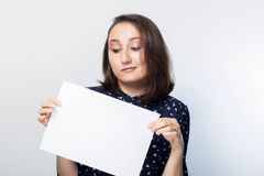 Jovem mulher que guarda a placa do negócio do sinal, vazia sobre o fundo branco, Imagem de Stock Royalty Free