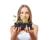 Jovem mulher que guarda a planta, broto do aipo Imagem de Stock Royalty Free