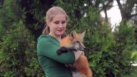 Jovem mulher que guarda a raposa e que levanta a parte dianteira da câmera fora filme