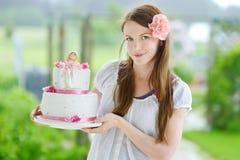 Jovem mulher que guarda seu bolo de aniversário fotos de stock