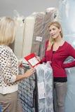 Jovem mulher que guarda a tabela de preços ao olhar a mãe na loja de móveis imagens de stock royalty free
