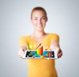 Jovem mulher que guarda a tabuleta com gráficos e diagramas coloridos Imagens de Stock Royalty Free