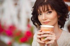 Jovem mulher que guarda um copo de papel e um sorriso Fotografia de Stock Royalty Free