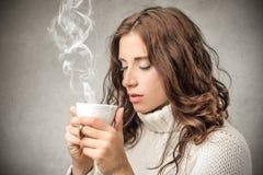 Jovem mulher que guarda um copo quente Fotografia de Stock Royalty Free