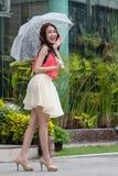 Jovem mulher que guarda um guarda-chuva. Fotografia de Stock Royalty Free