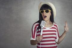 Jovem mulher que guarda um microfone que canta imagens de stock royalty free