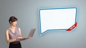 Jovem mulher que guarda um portátil e que apresenta a bolha moderna do discurso Fotografia de Stock