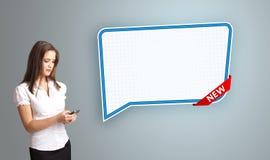 Jovem mulher que guarda um telefone e que apresenta a bolha moderna do discurso Imagem de Stock