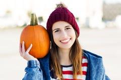 Jovem mulher que guarda uma abóbora Foto de Stock Royalty Free