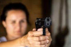 Jovem mulher que guarda uma arma e apontar fotografia de stock