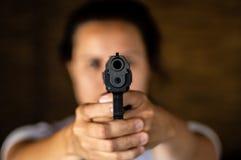 Jovem mulher que guarda uma arma e apontar fotografia de stock royalty free
