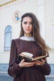 Jovem mulher que guarda uma Bíblia Fotos de Stock Royalty Free