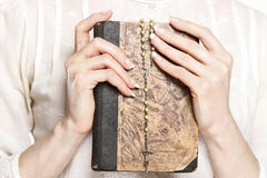Jovem mulher que guarda uma Bíblia Sagrada e um rosário Imagem de Stock