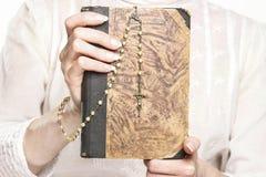 Jovem mulher que guarda uma Bíblia Sagrada e um rosário Fotografia de Stock Royalty Free