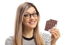 Jovem mulher que guarda uma barra e um sorriso mordidos de chocolate Foto de Stock Royalty Free