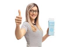 Jovem mulher que guarda uma caixa do leite e que faz um polegar acima do sinal fotografia de stock royalty free