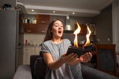 A jovem mulher que guarda uma carteira, carteira no fogo, menina surpreendida, foco m?gico do conceito, carteira ? fogo ardente imagens de stock royalty free