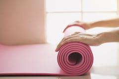 Jovem mulher que guarda uma esteira da ioga na classe do exercício imagens de stock