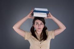 Jovem mulher que guarda uma pilha de livros em sua cabeça Imagens de Stock Royalty Free
