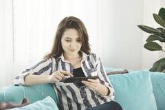 Jovem mulher que guarda uma tabuleta digital em casa imagens de stock royalty free