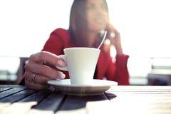 Jovem mulher que guarda uma xícara de café quente ao falar com seu telefone celular que senta-se no terraço da loja do coffe fotos de stock