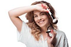 Jovem mulher que guardam a escova da composição e ruge isolado no branco foto de stock royalty free