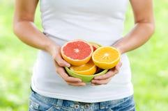 Jovem mulher que guardara laranjas e pamplumossas enchidas bacia Fotos de Stock