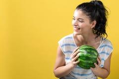 Jovem mulher que guardara a melancia fotos de stock