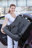 Jovem mulher que guardara o assento infantil da segurança Imagens de Stock Royalty Free