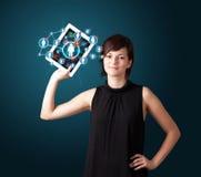 Jovem mulher que guardara a tabuleta com ícones sociais da rede Foto de Stock