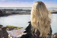 Jovem mulher que guardara um mapa Fotografia de Stock Royalty Free