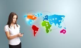 Jovem mulher que guardara um telefone e que apresenta o mapa do mundo colorido foto de stock