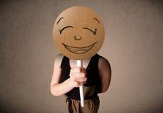 Jovem mulher que guardara uma placa da cara do smiley Imagem de Stock
