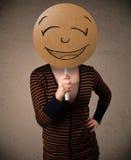 Jovem mulher que guardara uma placa da cara do smiley Foto de Stock