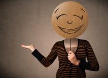 Jovem mulher que guardara uma placa da cara do smiley Fotografia de Stock
