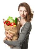 Jovem mulher que guardara vegetais e frutos no saco de compras Imagens de Stock