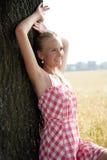 Jovem mulher que inclina-se em uma árvore Fotos de Stock Royalty Free