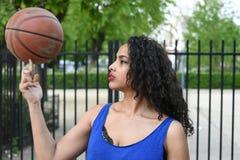 Jovem mulher que joga a bola da cesta na rua Foto de Stock Royalty Free
