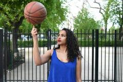 Jovem mulher que joga a bola da cesta na rua Fotografia de Stock