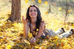 Jovem mulher que joga com folhas Fotos de Stock Royalty Free