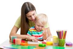 Jovem mulher que joga com seu menino com plasticine no fundo branco imagem de stock royalty free