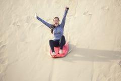 Jovem mulher que joga no estilo de vida exterior das dunas de areia fotografia de stock
