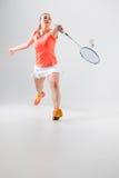 Jovem mulher que joga o badminton sobre o fundo branco Fotografia de Stock Royalty Free